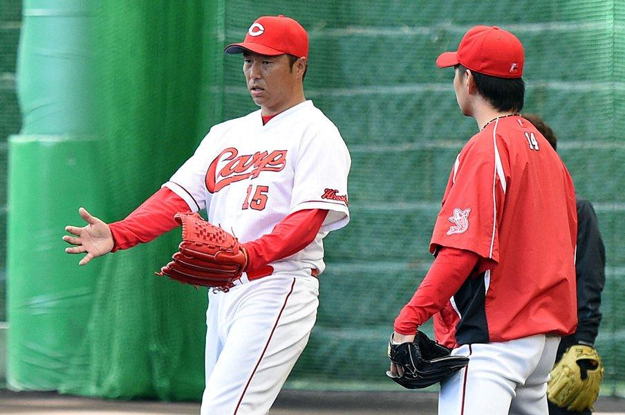 2月18日、大瀬良大地(右)にアドバイスをする黒田博樹。