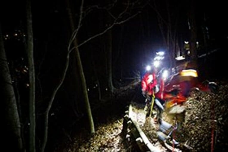 夜間、ヘッドライトをつけて山道を走っていくランナーたち。 / photograph by