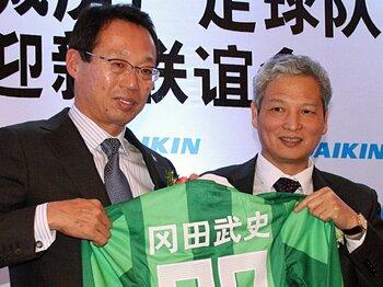 中国で開かれた、クラブの監督就任記者会見で自身の名前が入ったユニフォームを披露した岡田武史氏