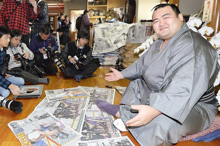 優勝から一夜明け、初優勝を報じるスポーツ新聞をズラリと並べた琴奨菊。