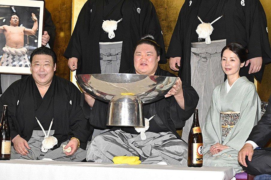 大相撲秋場所の全勝による初優勝を、大杯を抱えて祝う豪栄道。その側には境川親方が座る。